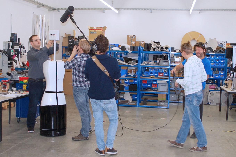 Inventur-Roboter TORY wird von einem Filmteam gefilmt.