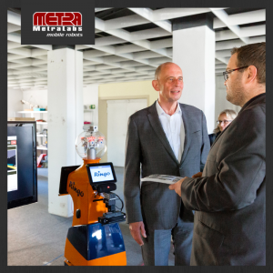 Wolfgang Tiefensee schaut sich mobilen Roboter in den Räumen der MetraLabs GmbH an